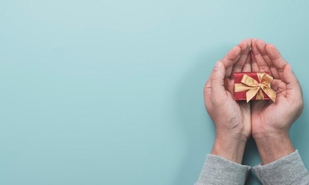 Geschäftsmann, der rote geschenkbox mit goldband für geschenk zum liebhaber, frohe weihnachten frohes neues jahr und valentinstag konzept hält.