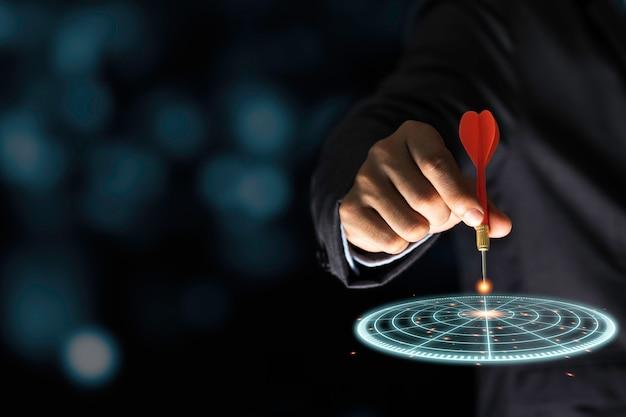 Geschäftsmann, der roten pfeilpfeil zur virtuellen zielpfeilplatte wirft. richten sie ziele und vorgaben für das geschäftsinvestitionskonzept ein.
