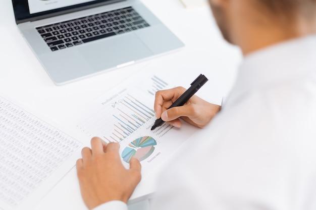 Geschäftsmann, der rückansicht der finanzdaten analysiert analyzing