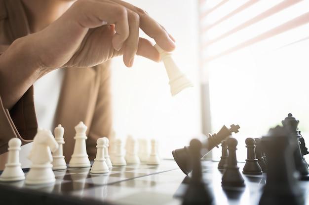 Geschäftsmann, der schach an bord im büro-, strategie- und wettbewerbskonzept spielt