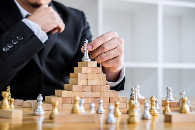 Geschäftsmann, der schachspiel zur entwicklungsanalyse neuer strategieplan spielt