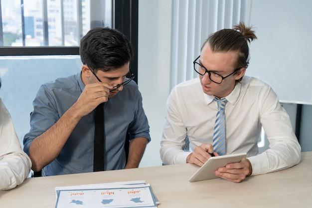 Geschäftsmann, der schockierende börsennachrichten auf digitaler tablette zeigt.