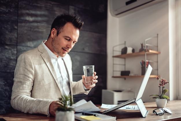 Geschäftsmann, der schreibarbeit in seinem büro tut und glas wasser hält