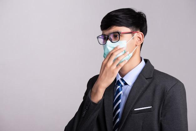 Geschäftsmann, der schützende gesichtsmaske, coronavirus und pm 2.5 kampfkonzept trägt.