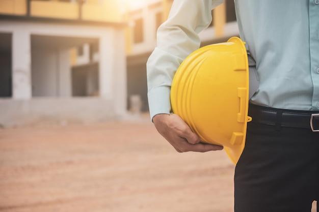 Geschäftsmann, der schutzhelmbau-erbaufbauhintergrund, ingenieuraufseher-vorarbeiterkonzept hält