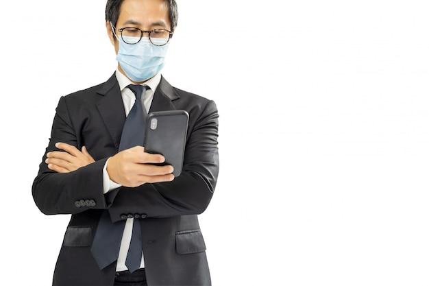 Geschäftsmann, der schutzmaske mit handy trägt