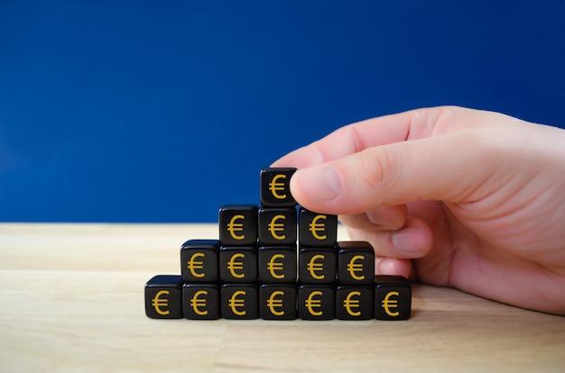 Geschäftsmann, der schwarze würfel mit gold-euro-zeichen in form einer pyramide in einem konzeptuellen bild des finanziellen wachstums zusammensetzt.