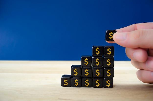 Geschäftsmann, der schwarze würfel mit golddollarzeichen in einer form des wachstumsgraphen in einem konzeptuellen bild des finanziellen wachstums zusammensetzt.