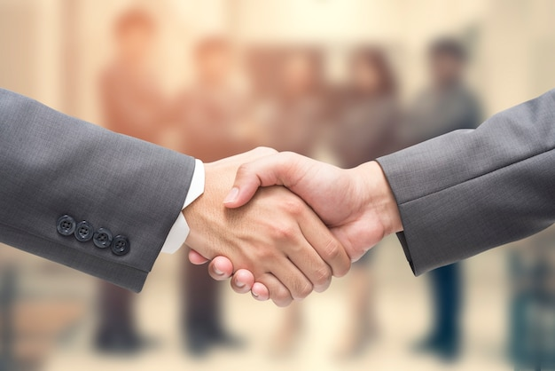 Geschäftsmann, der schwarzen anzug business handshake trägt