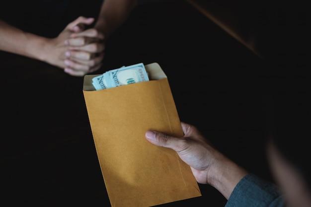 Geschäftsmann, der schwarzes geld im umschlag ablehnt, der vom auftragnehmer für erlaubnis im vertrag angeboten wird.