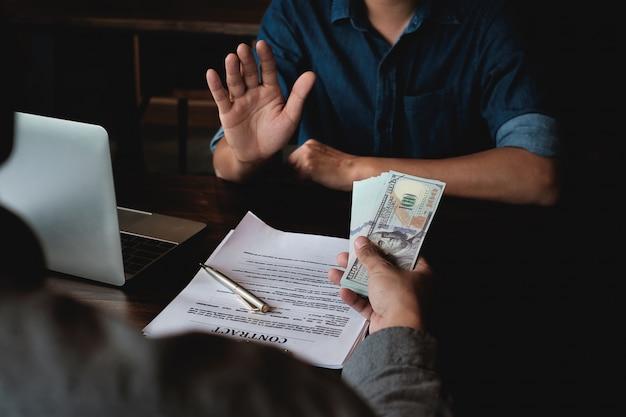Geschäftsmann, der schwarzgeld zurückweist, das vom auftragnehmer für erlaubnis im vertrag angeboten wird.