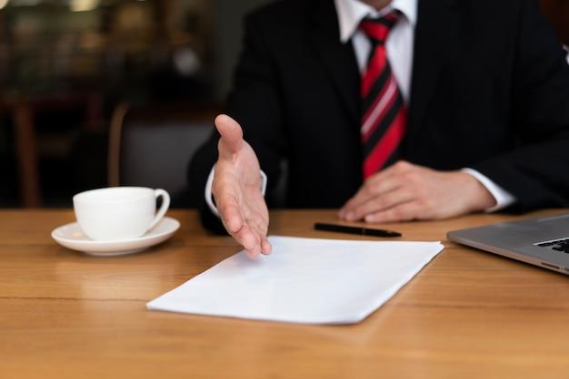 Geschäftsmann, der sein abkommen im büro darstellt