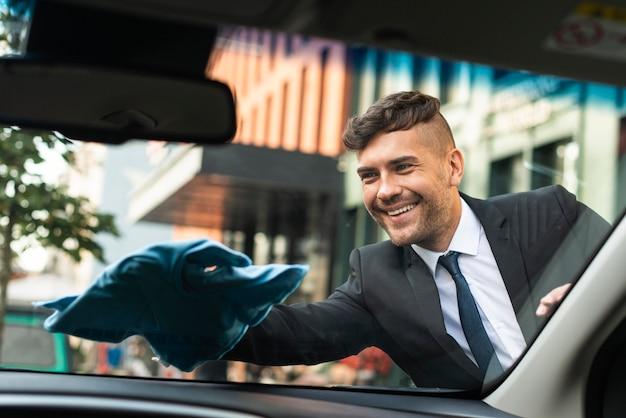 Geschäftsmann, der sein auto reinigt