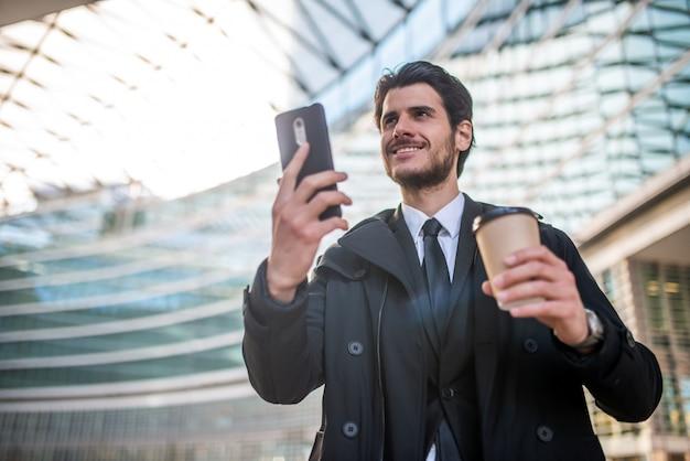 Geschäftsmann, der sein smartphone beim kaffeetrinken beobachtet