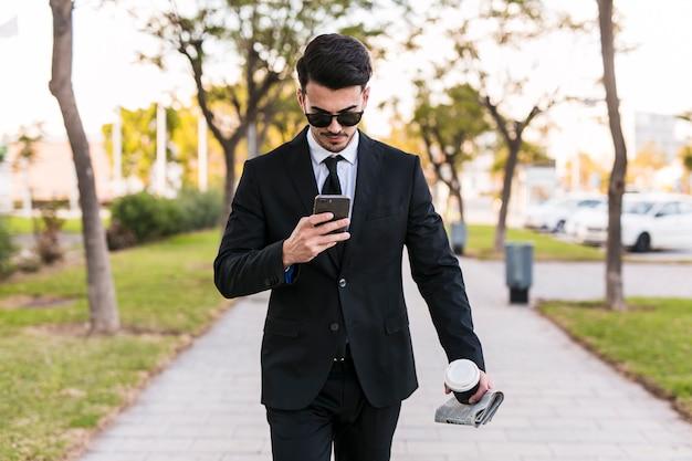 Geschäftsmann, der sein telefon auf den park betrachtet