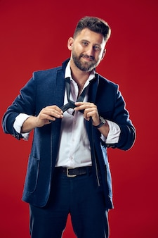 Geschäftsmann, der seine krawatte im studio bindet. lächelnder geschäftsmann, der isoliert auf rotem studio steht.