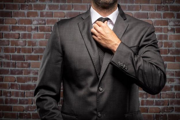 Geschäftsmann, der seine krawatte in einem gefängnis hält. konzept der korruption, korrupte politiker, illegale unternehmen. backsteinhintergrund.