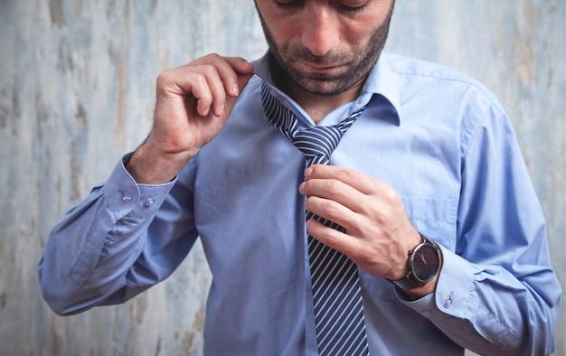 Geschäftsmann, der seine krawatte repariert. mode, lifestyle