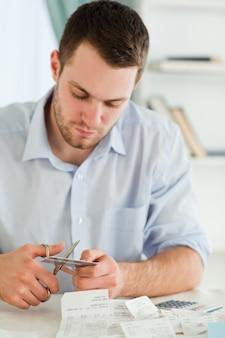 Geschäftsmann, der seine kreditkarte in stücke schneidet