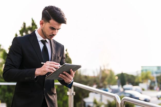 Geschäftsmann, der seine tablette verwendet