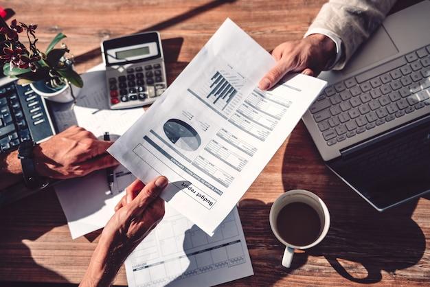 Geschäftsmann, der seinem mitarbeiter budgetbericht führt