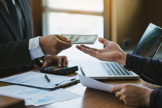 Geschäftsmann, der seinem partner am schreibtisch geld gibt