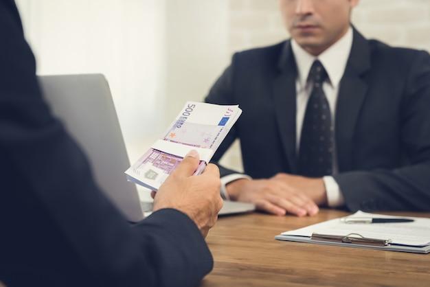 Geschäftsmann, der seinem partner geld, eurowährung am arbeitstisch gibt