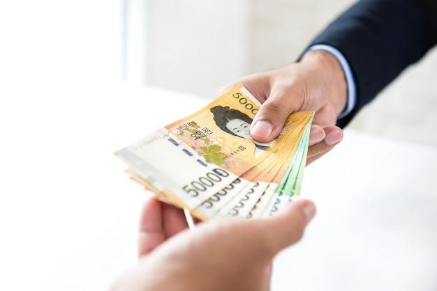 Geschäftsmann, der seinem partner geld, südkoreanische gewonnene währung gibt