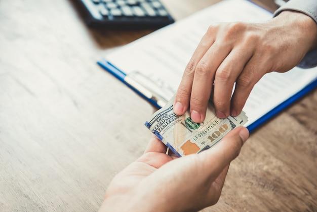 Geschäftsmann, der seinem partner geld, us-dollar, gibt, während er vertrag schließt