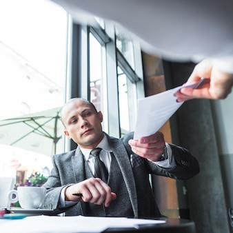 Geschäftsmann, der seinem partner in café dokument gibt
