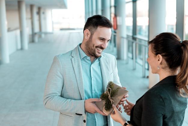 Geschäftsmann, der seinem weiblichen mitarbeiter geschenk gibt.