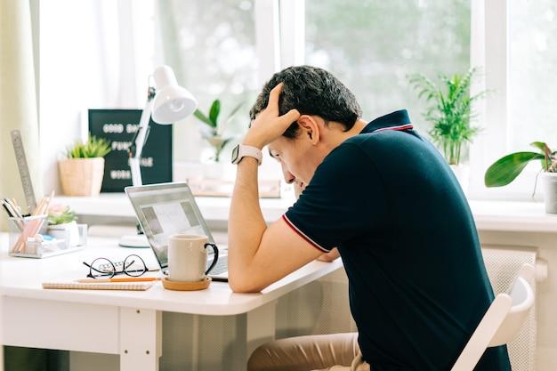 Geschäftsmann, der seinen kopf hält, arbeiten in einem laptop