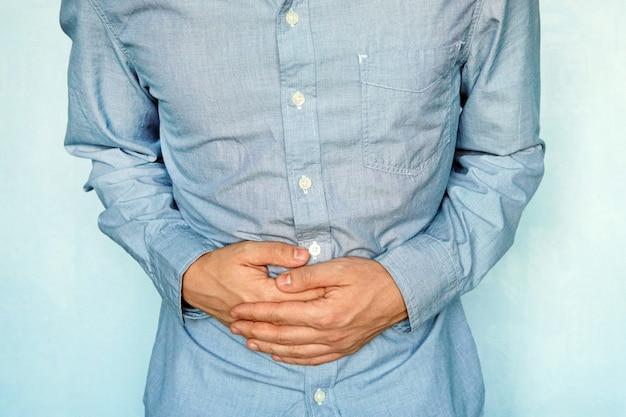 Geschäftsmann, der seinen magen vor schmerzen hält. schweregefühl im magen nach dem essen. erkrankungen des magen-darm-traktes. gase im magen. magenreizung. probleme mit dem verdauungsprozess