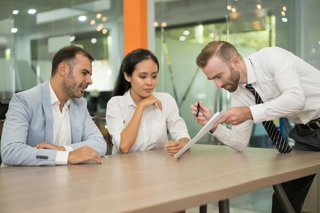 Geschäftsmann, der seinen mitarbeitern idee im büro darstellt