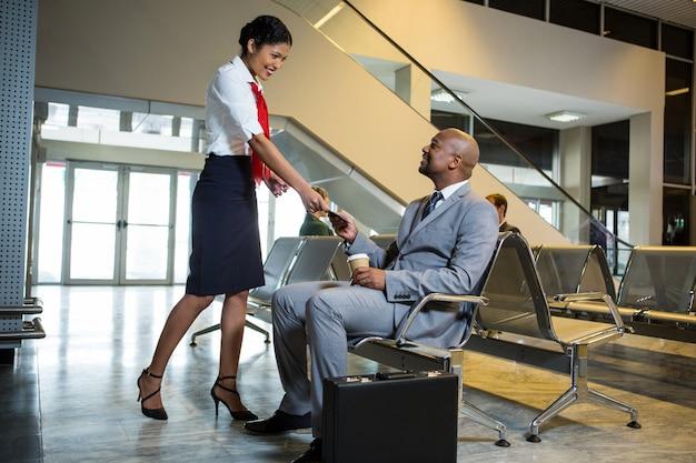 Geschäftsmann, der seinen pass zum wartebereich des check-in der fluggesellschaft gibt