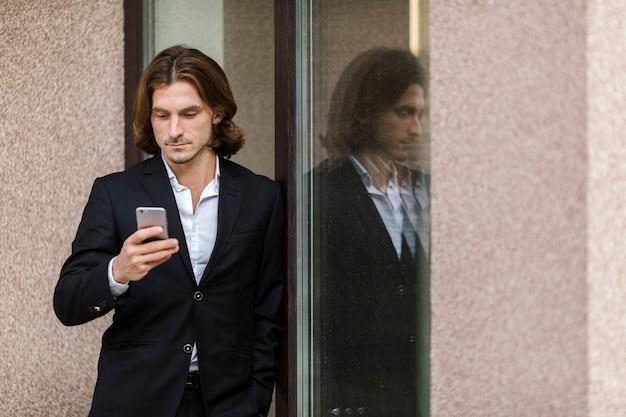 Geschäftsmann, der seinen telefonmediumschuß überprüft