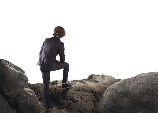 Geschäftsmann, der sich auf einen felsen stützt und den horizont beobachtet