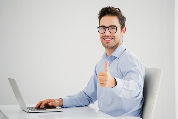 Geschäftsmann, der sich daumen bei der anwendung des laptops zeigt