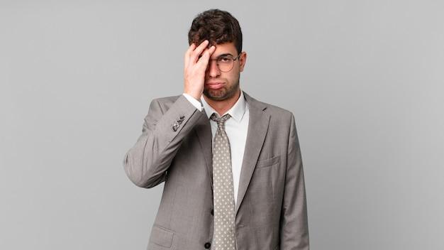Geschäftsmann, der sich nach einer ermüdenden, langweiligen und mühsamen aufgabe gelangweilt, frustriert und schläfrig fühlt und das gesicht mit der hand hält