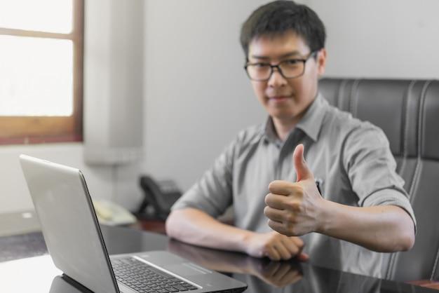 Geschäftsmann, der sich seinen daumen, leute-feier-erfolgs-arbeitendes erfolgreiches konzept zeigt