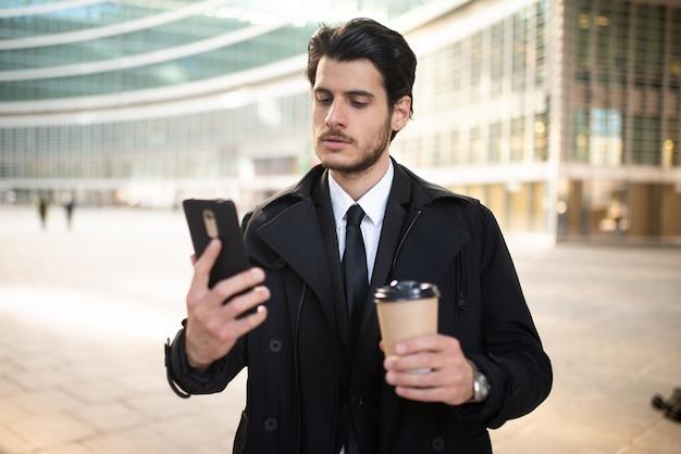 Geschäftsmann, der smartphone beim kaffeetrinken beobachtet