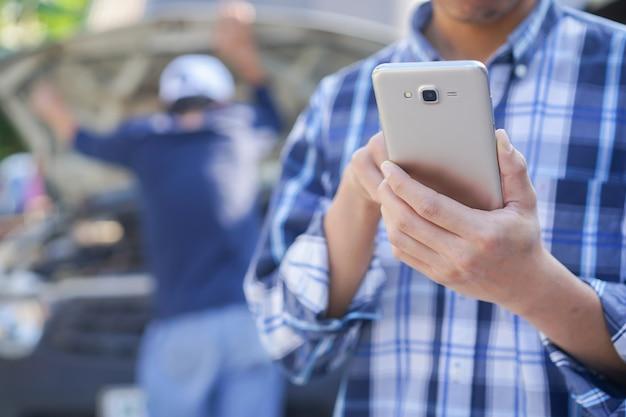 Geschäftsmann, der smartphone für service des technikerfestlegungsautos hält