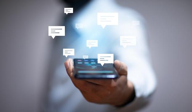Geschäftsmann, der smartphone mit buchstabenschildern hält