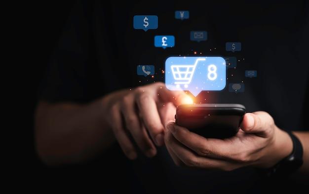 Geschäftsmann, der smartphone mit einkaufswagen hält, um neue bestellung für das online-shopping-konzept einzugeben.