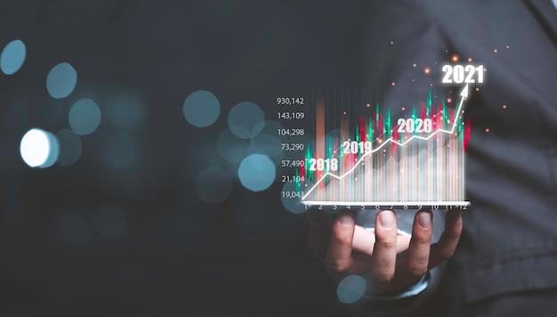 Geschäftsmann, der smartphone mit info-grafik virtuelles geschäftsinvestitionsdiagramm und kopienraum hält.