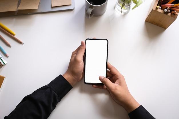Geschäftsmann, der smartphone mit leerem bildschirm auf woonden schreibtisch verwendet