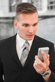 Geschäftsmann, der smartphone mit überraschtem ausdruck betrachtet