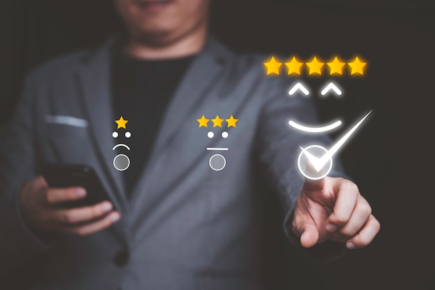 Geschäftsmann, der smartphone verwendet und lächelnknopf für die beste bewertung, kundenzufriedenheitskonzept drückt.