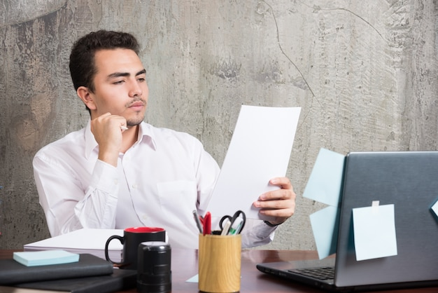 Geschäftsmann, der sorgfältig arbeitspapiere am schreibtisch liest.