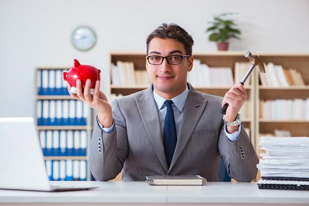 Geschäftsmann, der sparschwein im büro bricht
